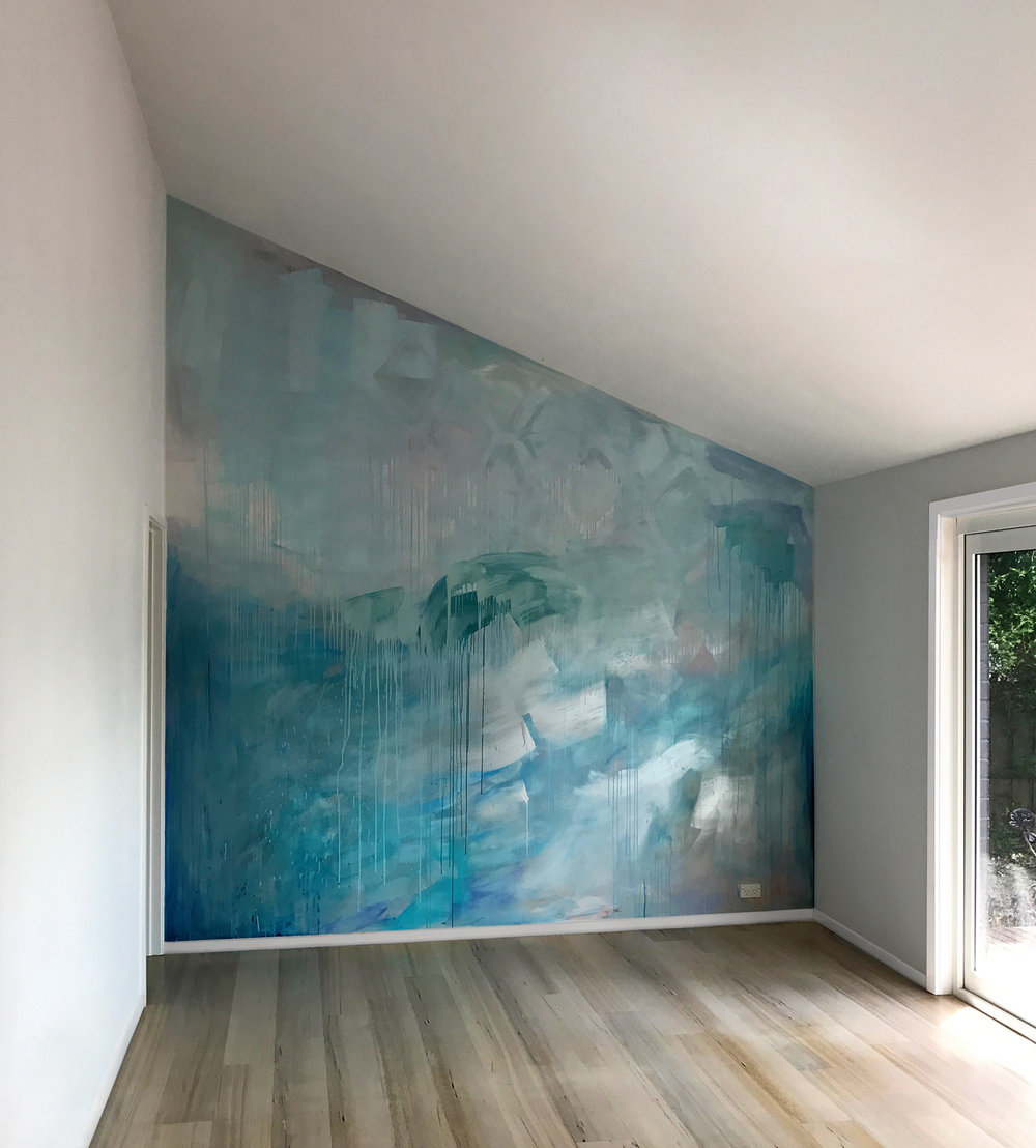 Ocean water painted contemporary abstract mural in pastel blue, green and metallic paint, featuring a wave, drips and geometric shapes, the artwork has movement and reflects light in the living room.