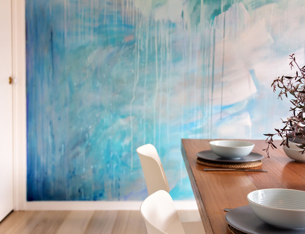 Ocean water painted contemporary abstract mural in kitchen featuring a custom built wooden table styled with kitchenware, the artwork has movement and reflects light.