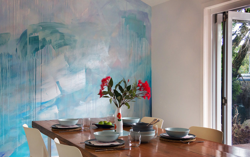 Ocean water painted contemporary abstract mural in kitchen featuring a custom built wooden table styled with kitchenware and native Australian flowers.
