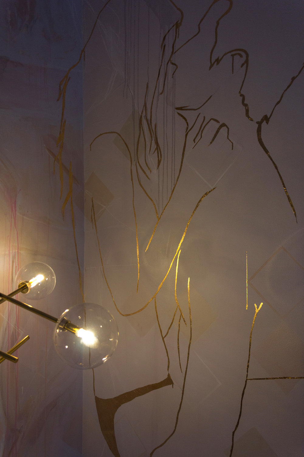 Mural featuring gold leaf outline of couple in love - male figure holds his girlfriend in his arms and they stare into each others eyes. A gold floor lamp illuminates the image.