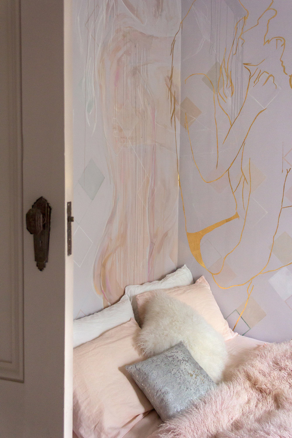 Mural featuring gold leaf outline of couple in love - male figure holds his girlfriend in his arms and they stare into each others eyes. Cosy bed with peach linen and a Mongolian sheepskin throw is styled in front.