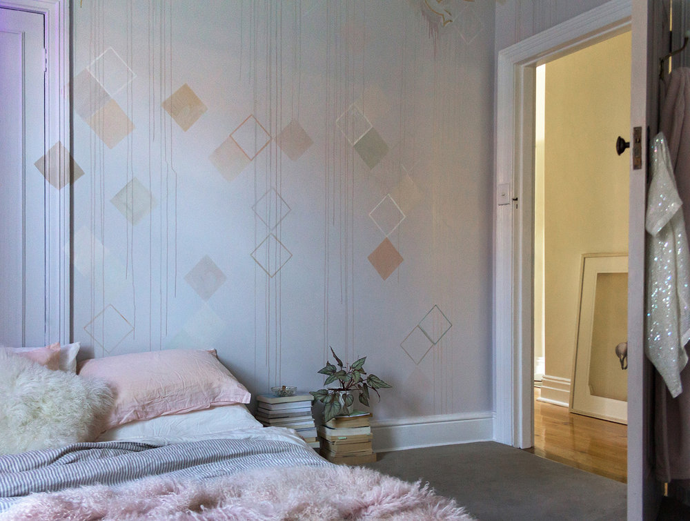 Pastel bedroom mural featuring geometric shapes and dripping paint. The bed is made with linen bedding and a soft, pink throw.