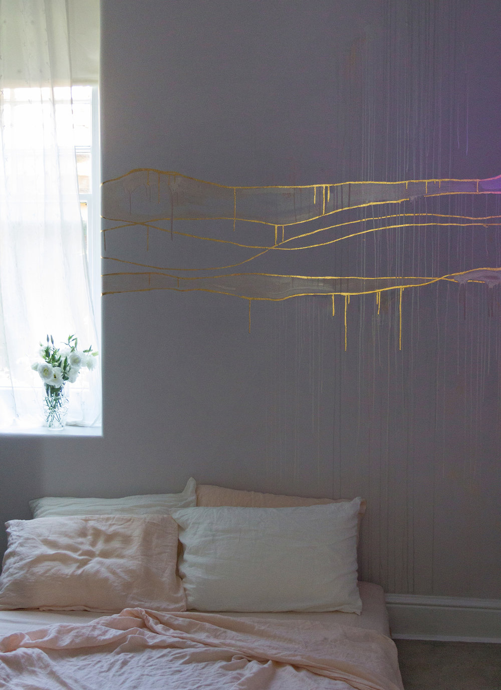 Gold leaf feature wall in cosy bedroom, the metallic paint is lit up with coloured lights.
