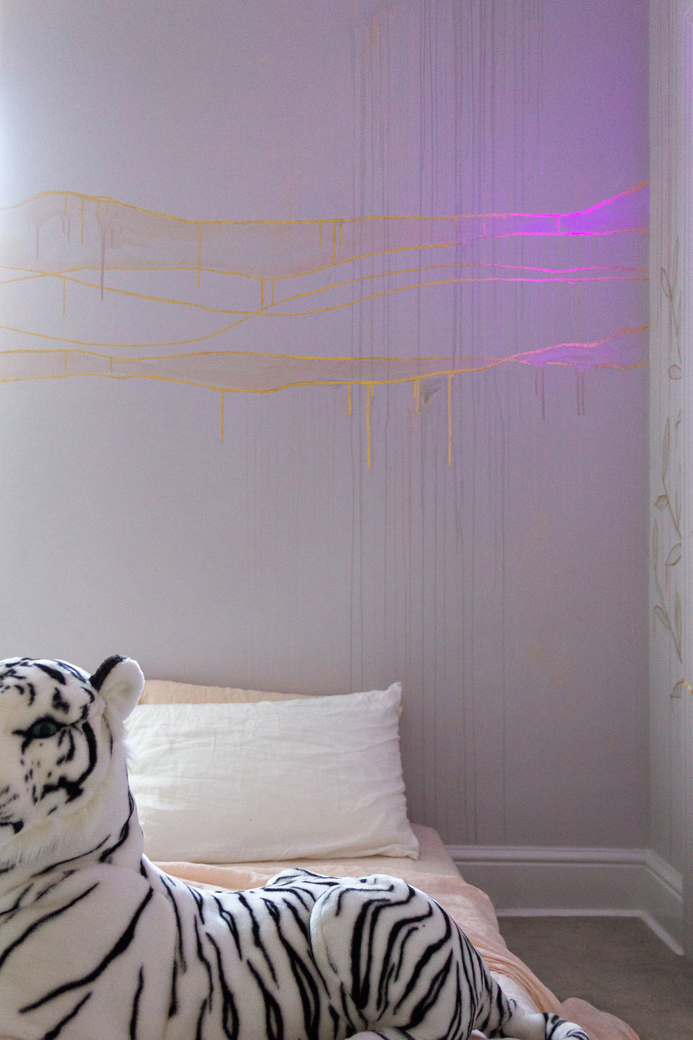 Gold leaf feature wall in cosy bedroom, the wall features waves lit up by purple light. In the foreground is a toy black and white tiger.