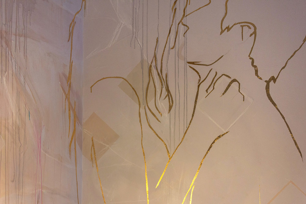 Mural featuring gold leaf outline of couple in love - male figure holds his girlfriend in his arms while they stare into each others eyes.