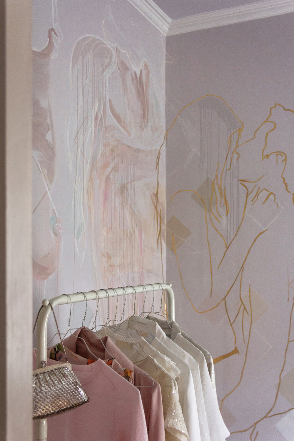Mural featuring gold leaf outline of couple in love - male figure holds his girlfriend in his arms and they stare into each others eyes. Clothing rack with pastel ladies clothing is styled in front.
