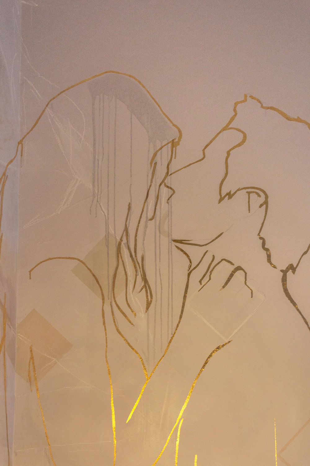 Mural featuring gold leaf outline of couple in love - male figure holds his girlfriend in his arms and they stare into each others eyes.