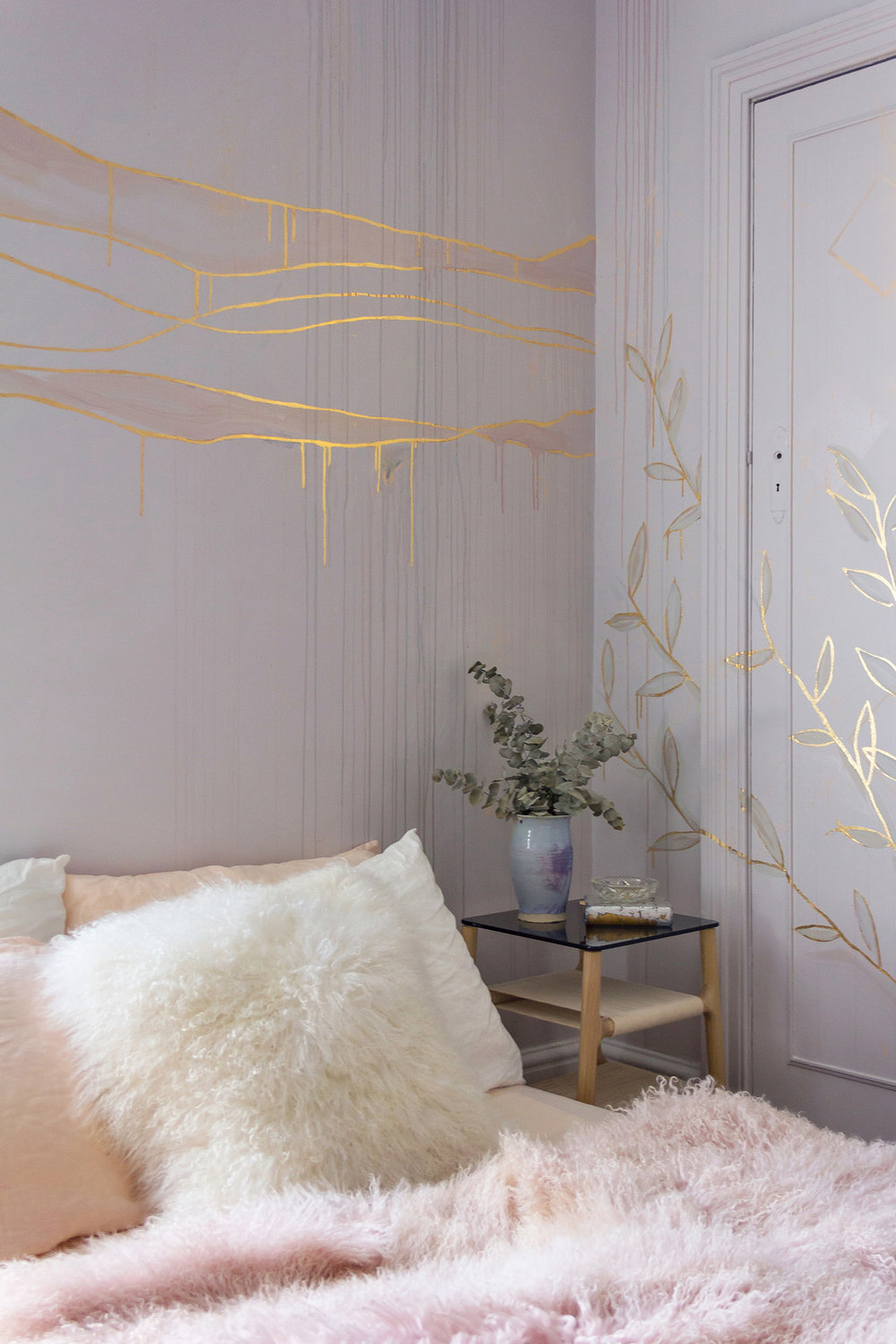 Gold leaf feature wall in cosy bedroom, the bed is made with peach linen sheets and a Mongolian sheepskin throw. Mural features gold waves and foliage.