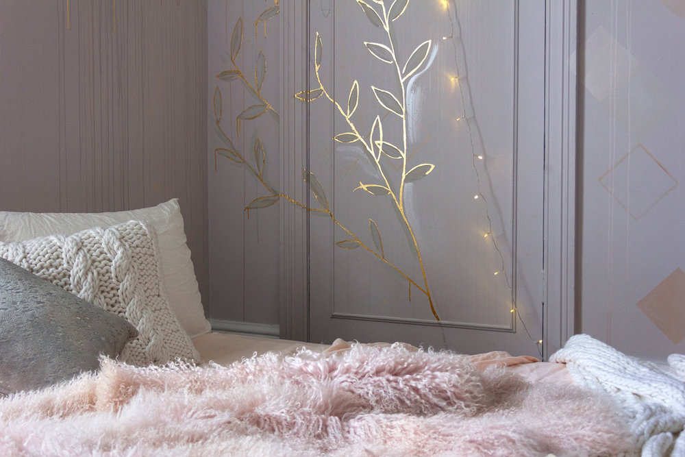 Gold leaf feature wall in cosy bedroom, the bed is made with peach linen sheets and a Mongolian sheepskin throw. Mural features gold leaf foliage and a string of fairy lights.