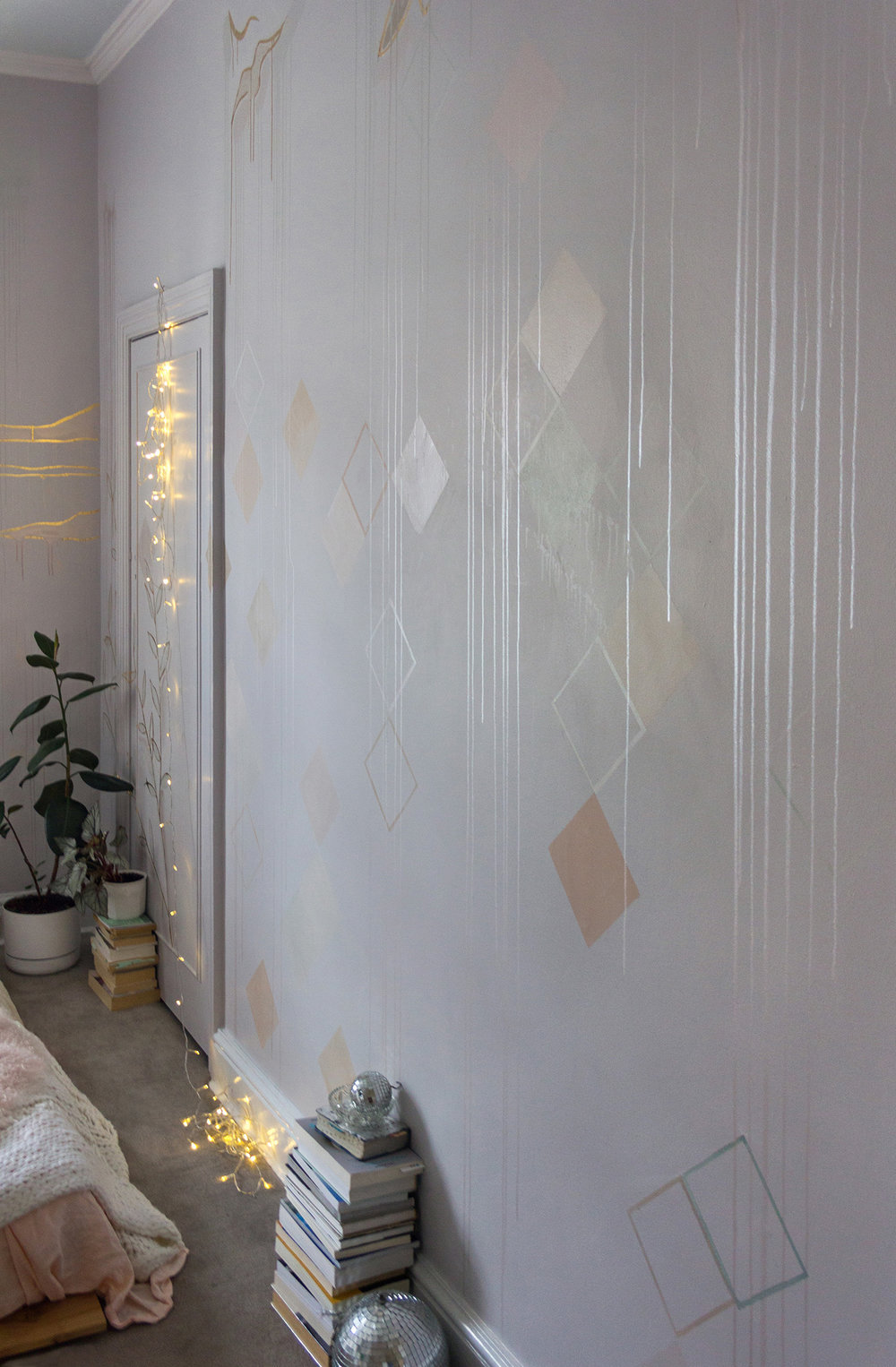 Cosy bedroom featuring a mural in pastel and metallic colours with gold leaf birds flying. Fairy lights provide a glow.