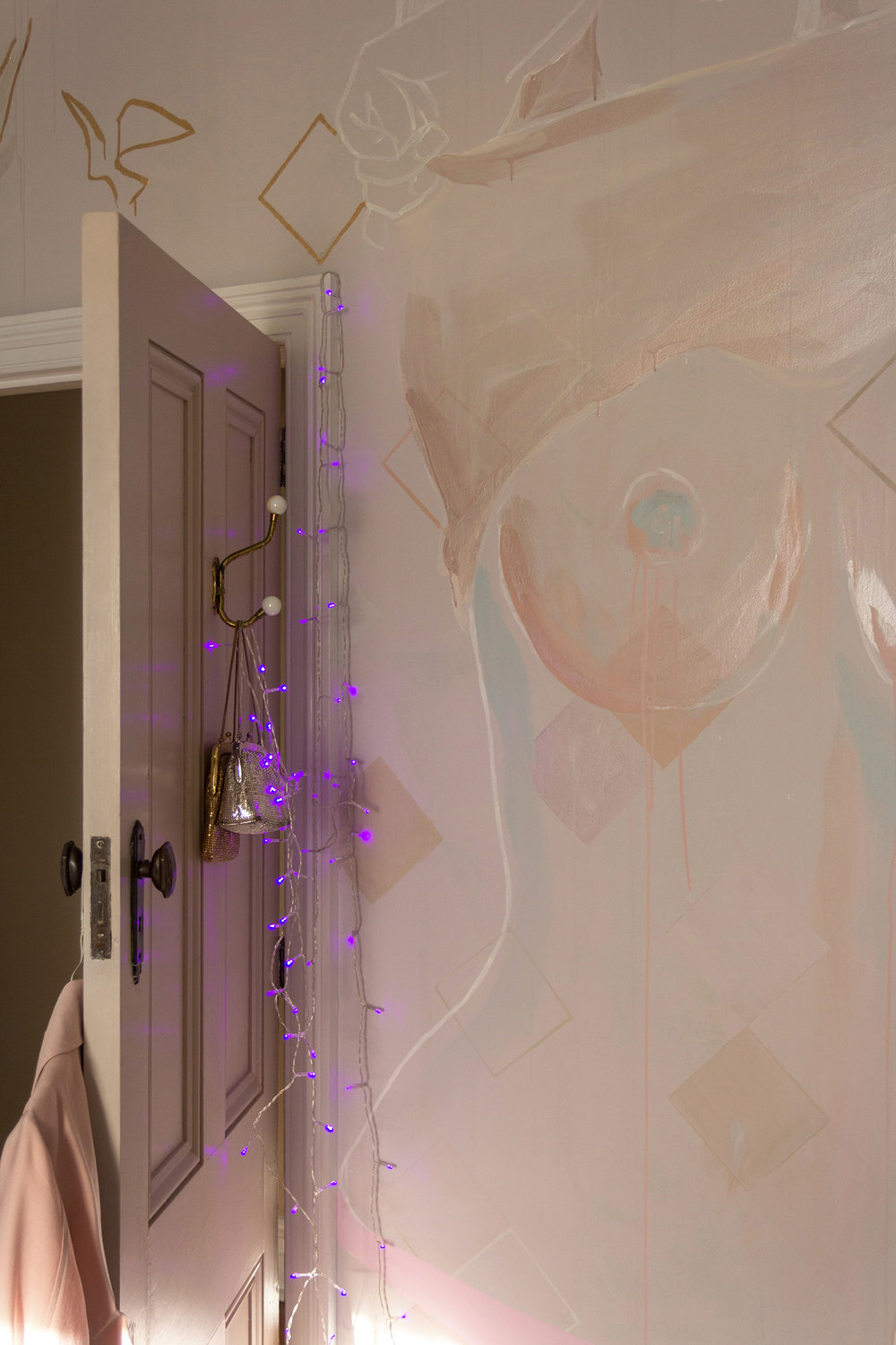 Topless woman mural - female is taking her top off and exposing her naked breasts. Painted in pastel and metallic colours with gold leaf birds flying out from the figure. Purple fairy lights glow around the bedroom door.