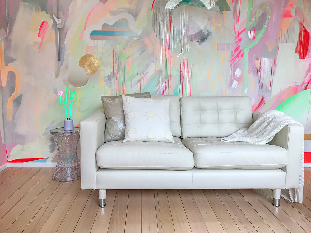 Vibrant galaxy wall mural in bright neon colours, featuring gold leaf shapes, metallic rainbow, spray painted cactus and striped cloud. Styled in front is a white leather couch and neon cactus lamp.