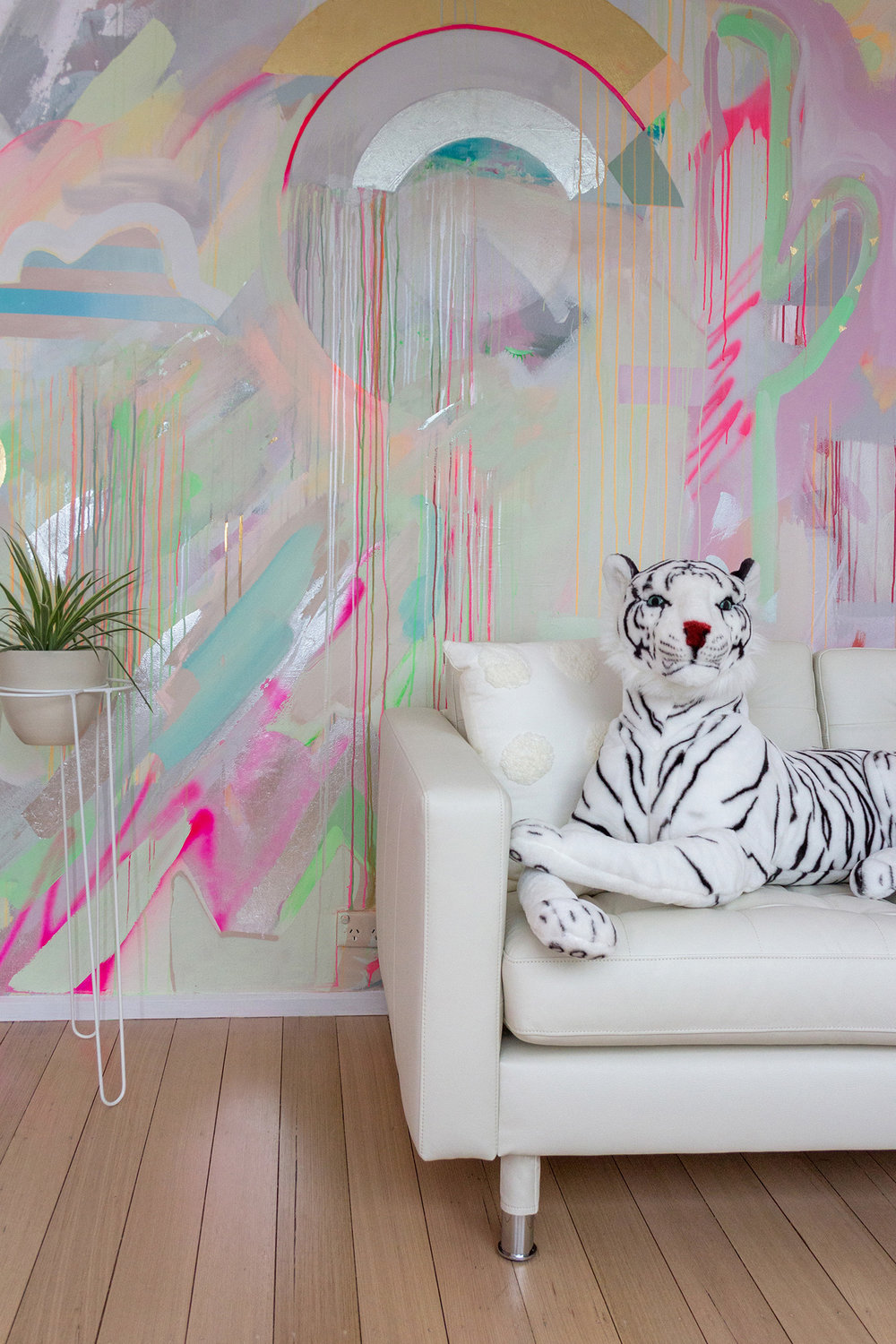 Vibrant galaxy wall mural in bright neon colours, featuring metallic rainbow, spray painted cactus and striped cloud. Styled in front is a white leather couch and black and white toy tiger.