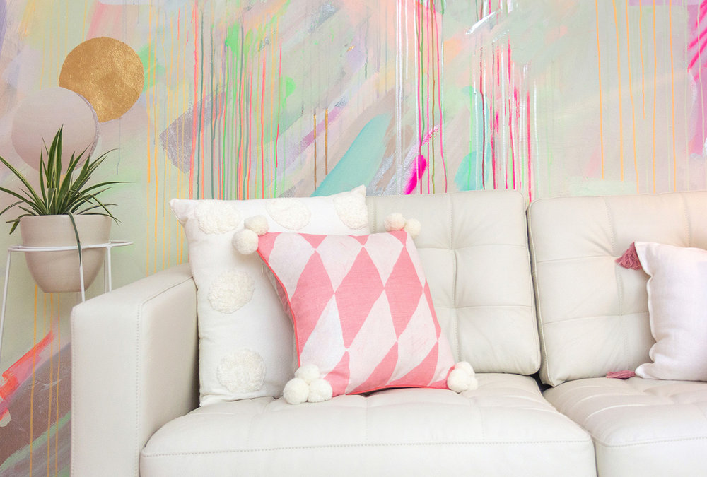 Vibrant wall mural in bright neon colours features behind a white leather couch and Bonnie and Neil pillow.