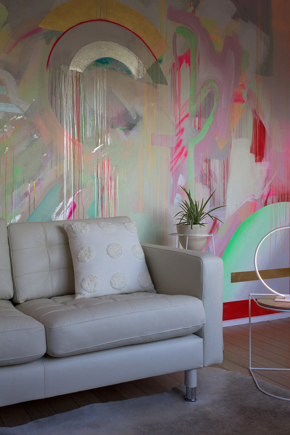 Vibrant galaxy wall mural in bright neon colours, featuring gold leaf shapes, metallic rainbow, spray painted cactus and striped cloud. Styled in front is a white leather couch and round LED lamp.