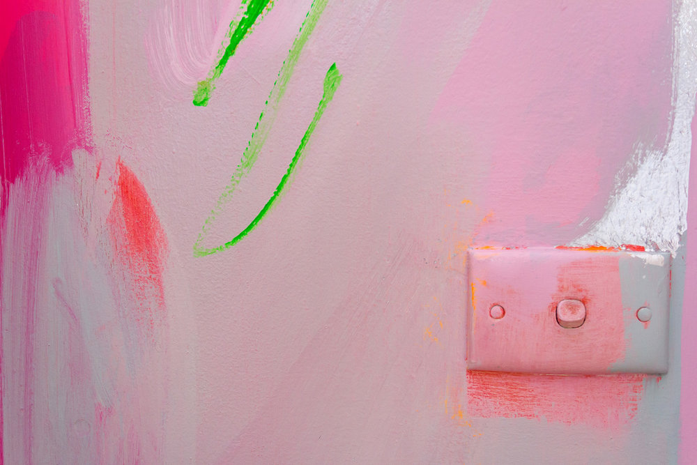 Close up of vibrant abstract mural in pink, green and pastel colours, emphasis on painted light switch.