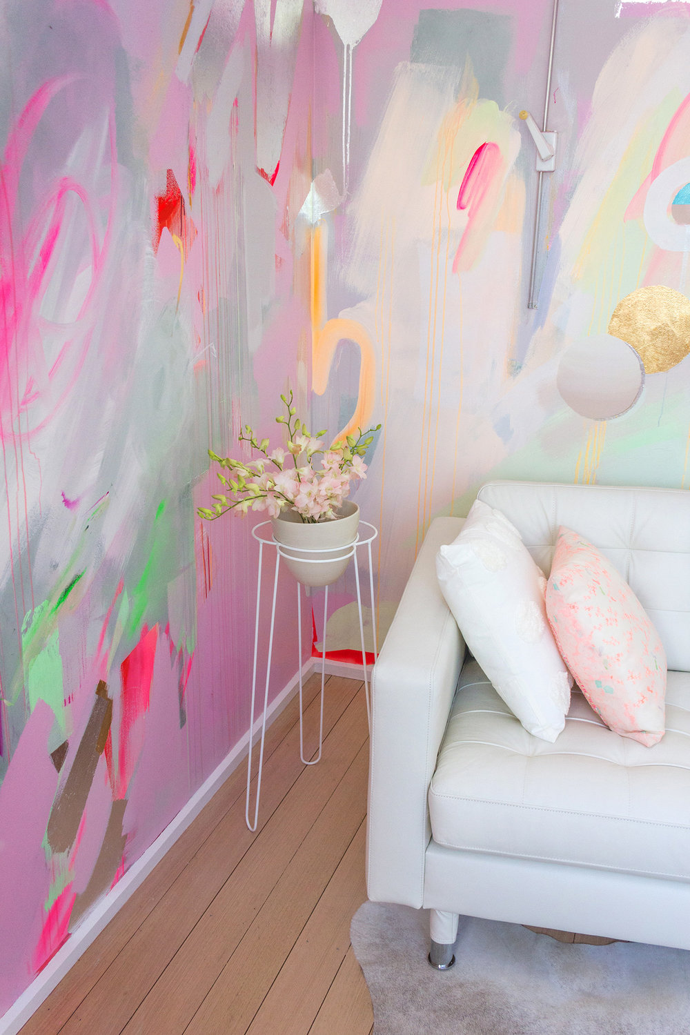 Vibrant abstract mural in pink, green and pastel colours. Light pink flowers feature in an Ivy Muse plant stand and pot while the corner of a white leather couch can be seen.