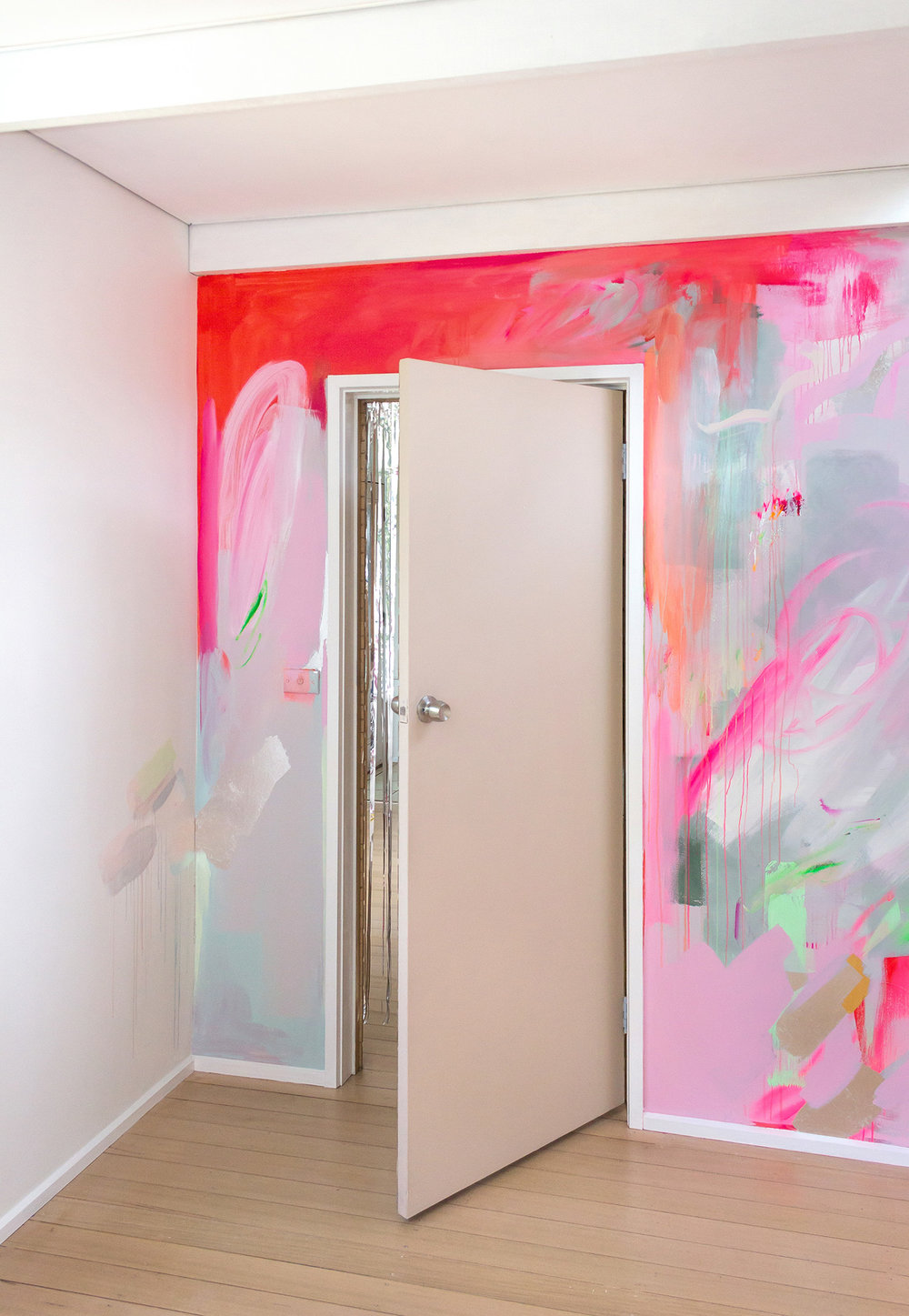 Vibrant abstract mural in pink, red and pastel colours. A silver metallic curtain peeks out from the doorway.