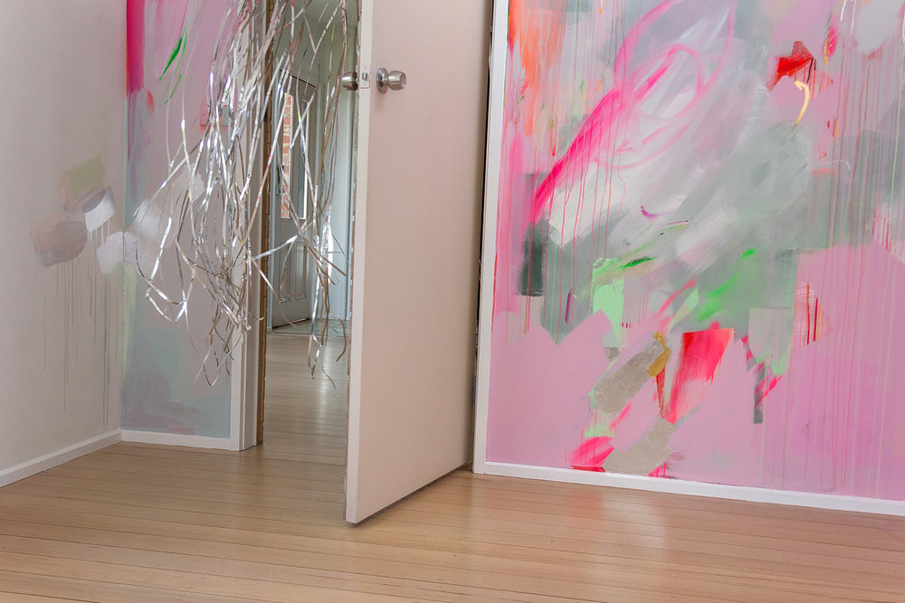 Vibrant abstract mural in pink, green and pastel colours, the energetic brushstrokes resemble a large butterfly A silver metallic curtain flies out from the doorway.