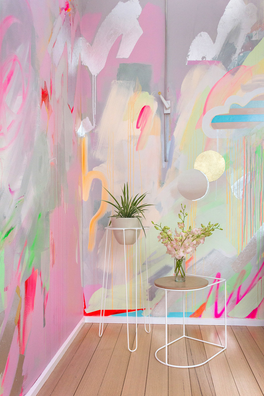 Vibrant abstract mural in pink, green and pastel colours, features silver metallic leaf shapes which create reflective surfaces. Painted motifs include a striped cloud and cactus. In front of the mural are two Ivy Muse plant stands that have been styled with plant life.
