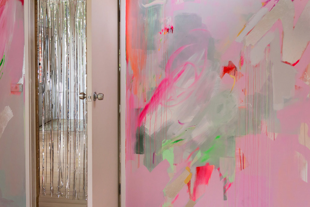 Vibrant abstract mural in pink, green and pastel colours, the energetic brushstrokes resemble a large butterfly A silver metallic curtain hangs in the doorway and silver metallic leaf shapes create reflective surfaces.
