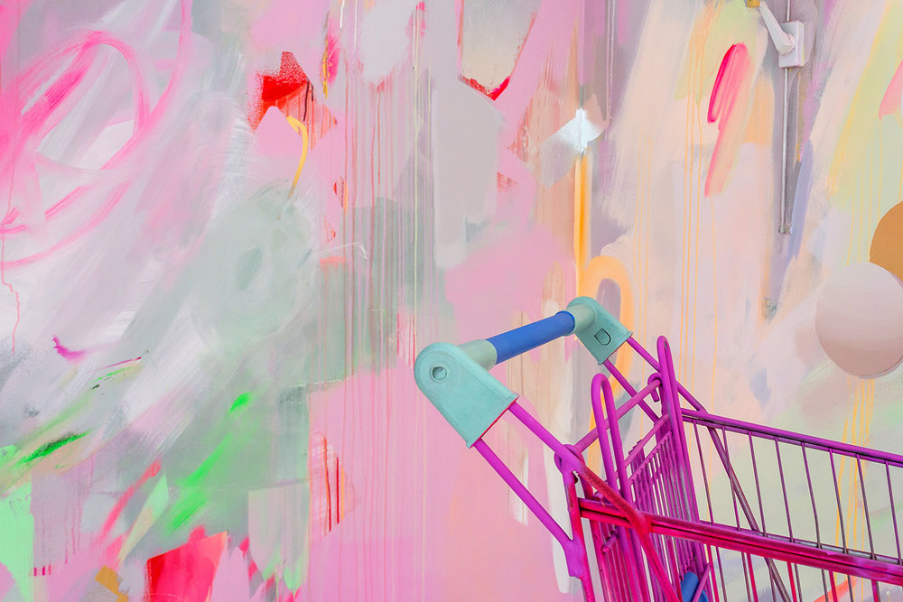 Vibrant abstract mural in pink, green and pastel colours, the energetic brushstrokes resemble a large butterfly A neon shopping trolley features in the foreground.