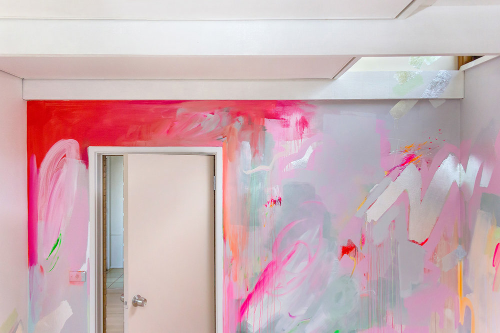 Vibrant abstract mural in pink, red and pastel colours. Silver leaf shapes provide interesting reflective surfaces.