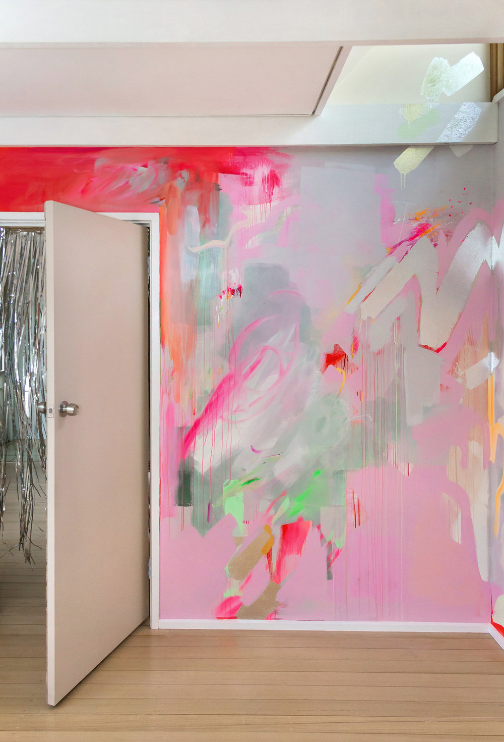 Vibrant abstract mural in pink, red, green and pastel colours, the energetic brushstrokes resemble a large butterlfy A silver metallic curtain flies out from the doorway and silver metallic leaf shapes create reflective surfaces.