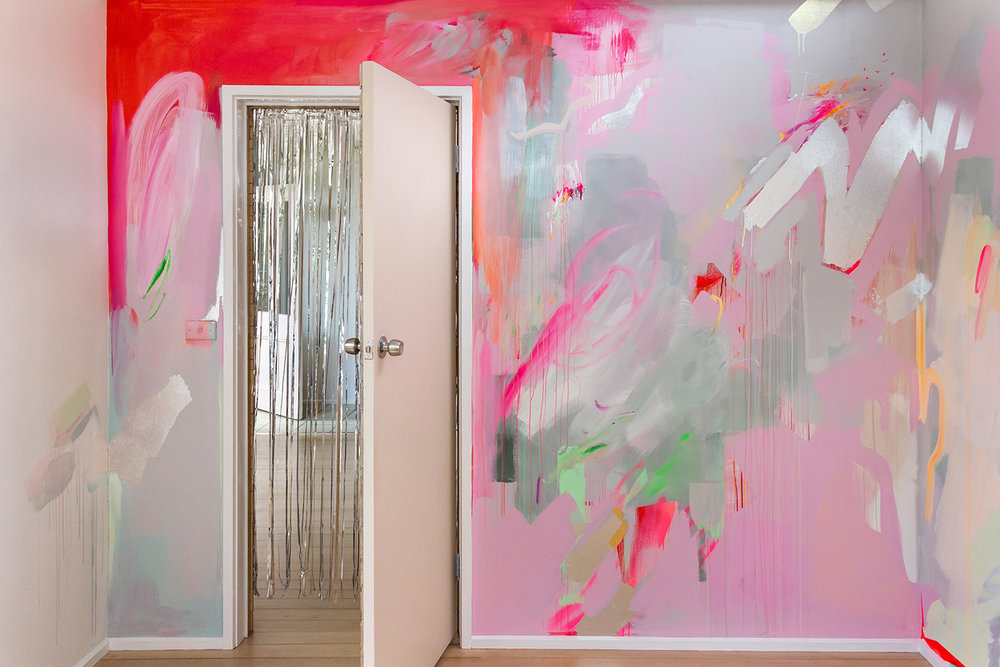 Vibrant abstract mural in pink, red, green and pastel colours, the energetic brushstrokes resemble a large butterfly A silver metallic curtain hangs in the doorway and silver metallic leaf shapes create reflective surfaces.