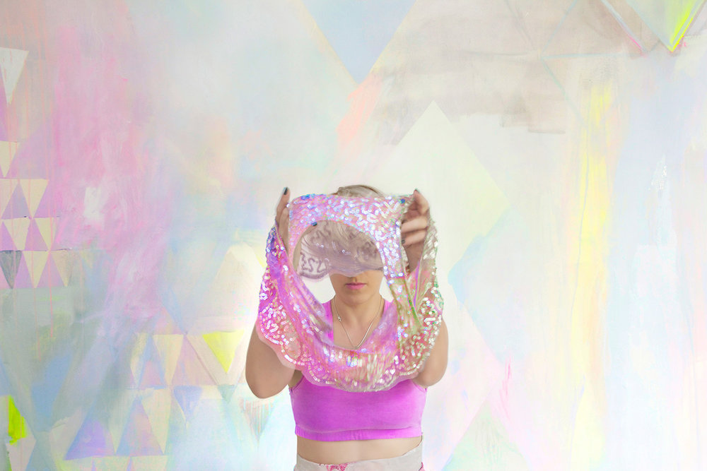 Playfully styled fashion shoot with diamond abstract pastel mural featuring metallic paint, triangles, geometric shapes and neon yellow highlights, models dresses in sparkly party crop top.
