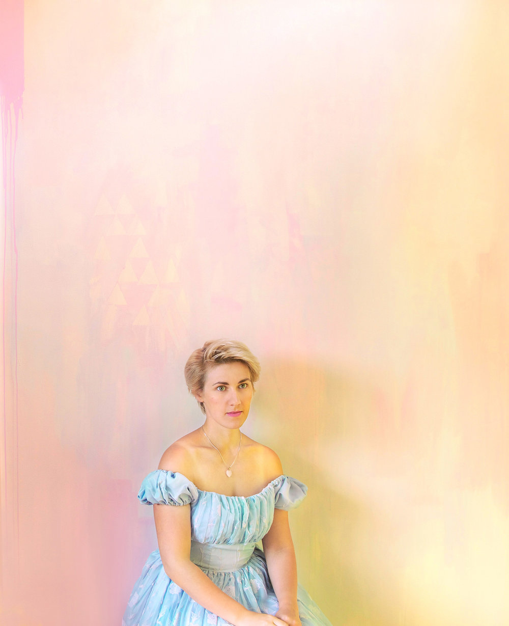 Alice in Wonderland theme styled interior featuring pastel abstract mural and portrait of Alice seated staring wistfully off camera, wearing off the shoulder blue princess dress and short blonde hair.