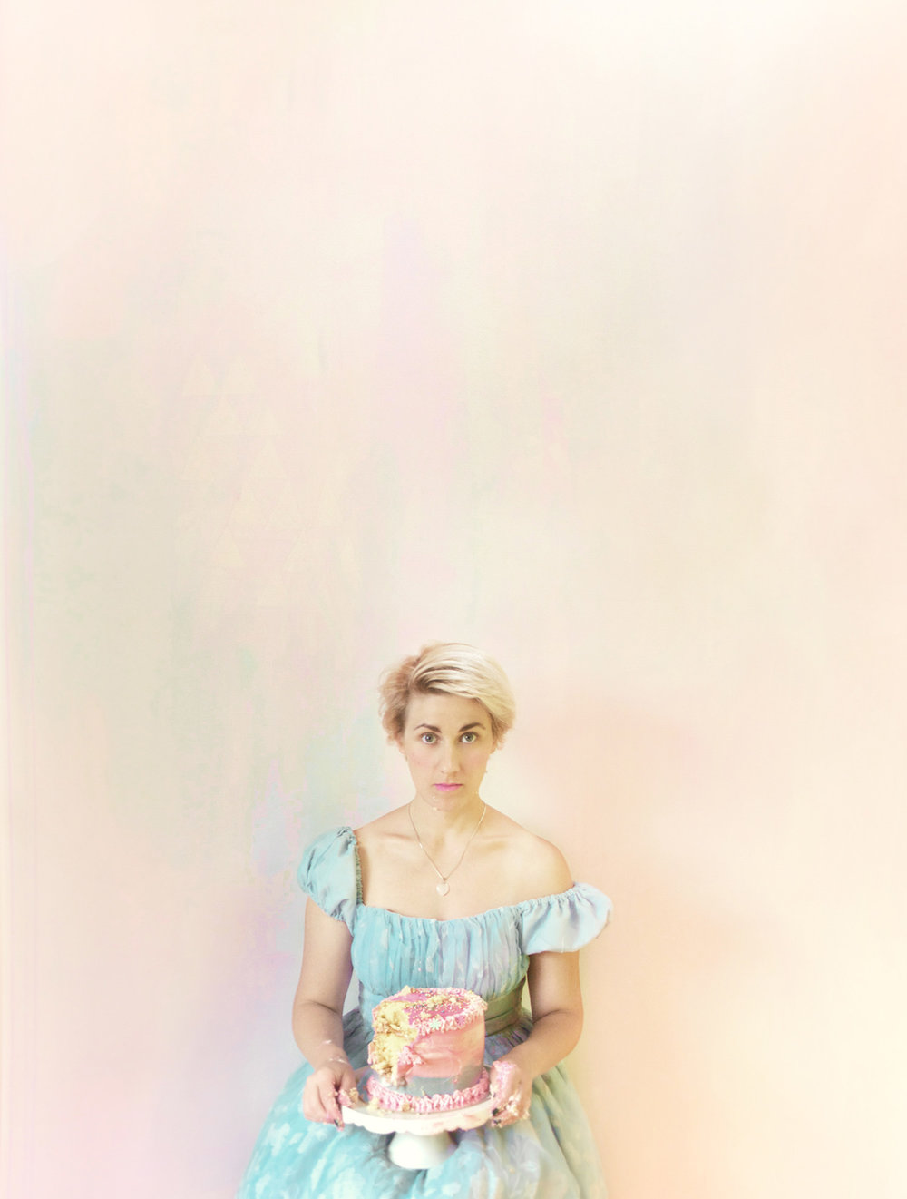 Alice in Wonderland party theme styled interior featuring pastel abstract mural and portrait of Alice holding a rainbow layer cake with sprinkles, cake has a handful missing, model wears off the shoulder blue princess dress and short blonde hair.