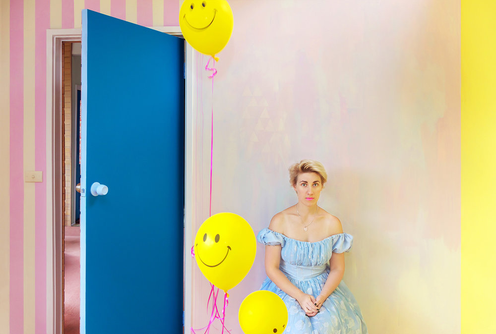 Alice in Wonderland party theme styled interior featuring pastel abstract mural and portrait of Alice wearing off the shoulder blue princess dress and short blonde hair, smiley face yellow helium balloons rise.