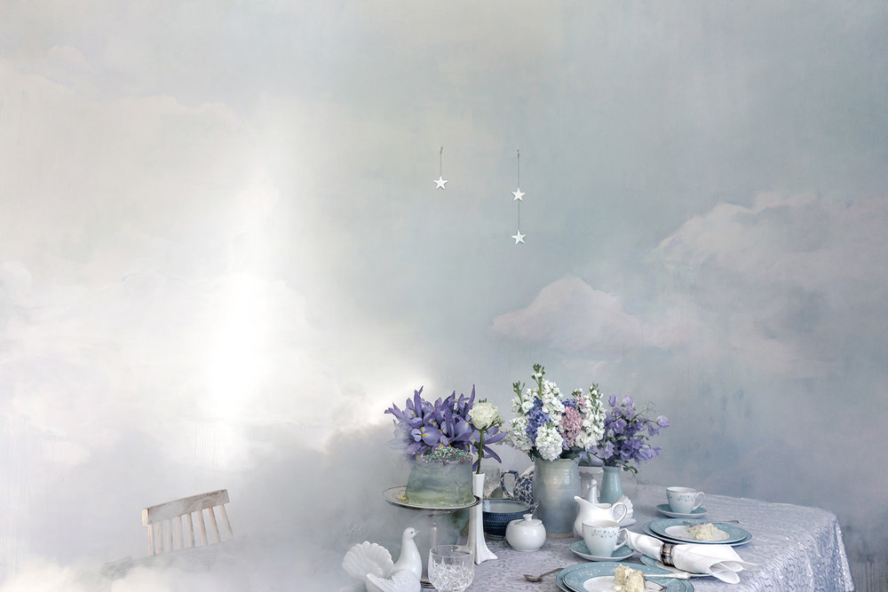 Dreamily styled dinner party in the clouds, with smoke machine and painted cloud mural in pastel tones, the table features flowers, dove and an iced vanilla layer cake.