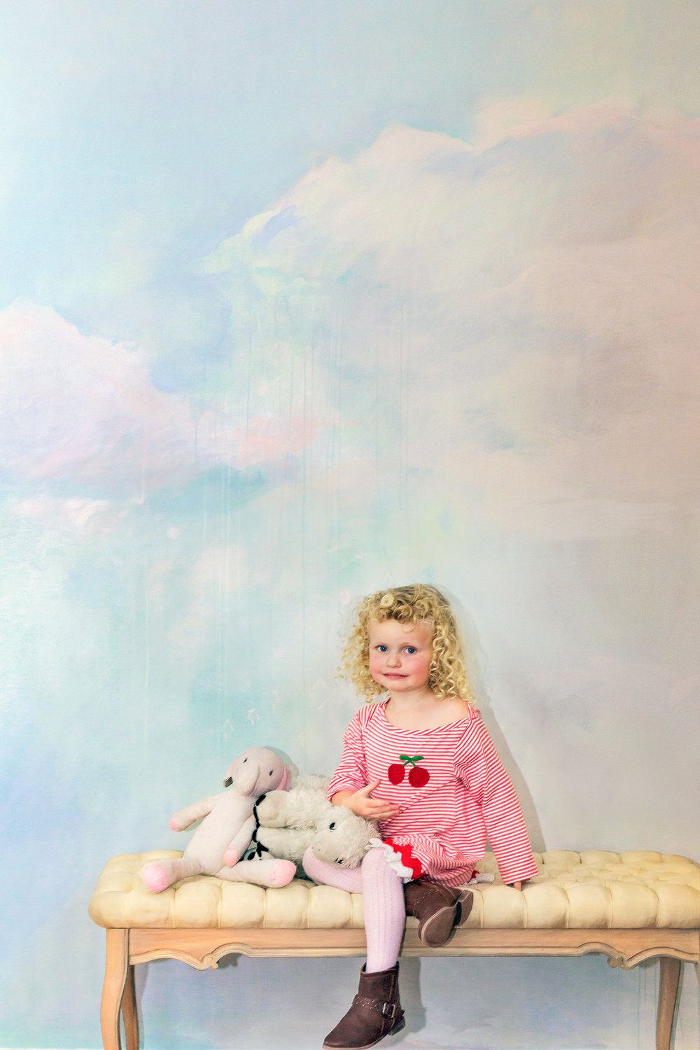 Dreamily styled children's bedroom idea, with painted cloud mural in pastel tones, blonde curly haired child model wears stripey cherry red dress and sits next to her stuffed toys.