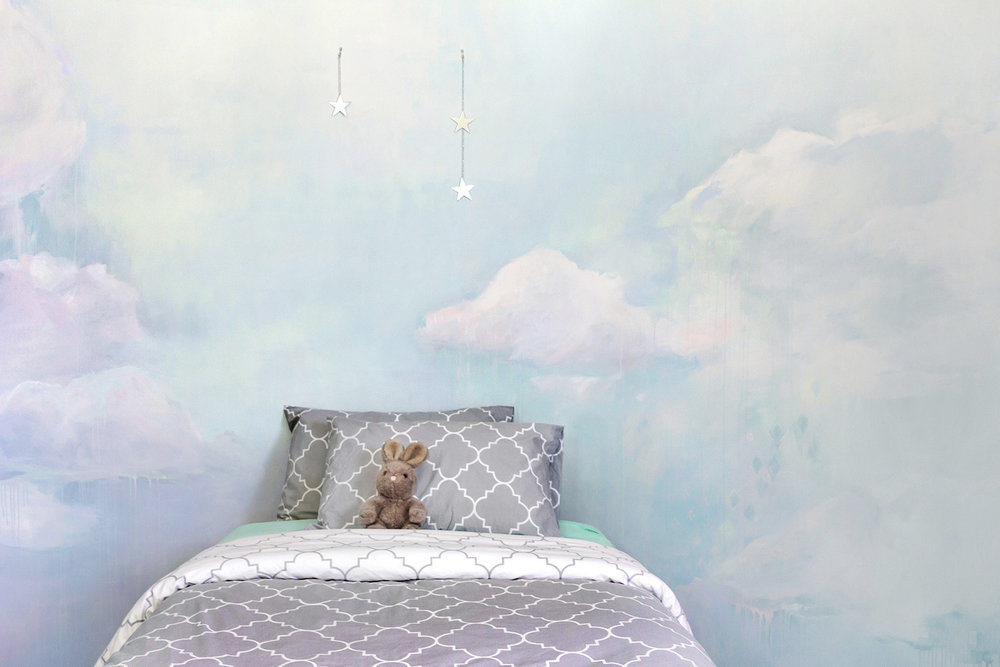 Dreamily styled children's bedroom with painted cloud mural, featuring pastel blue, pink and mint colors and bed with grey linen and bunny rabbit soft toy.