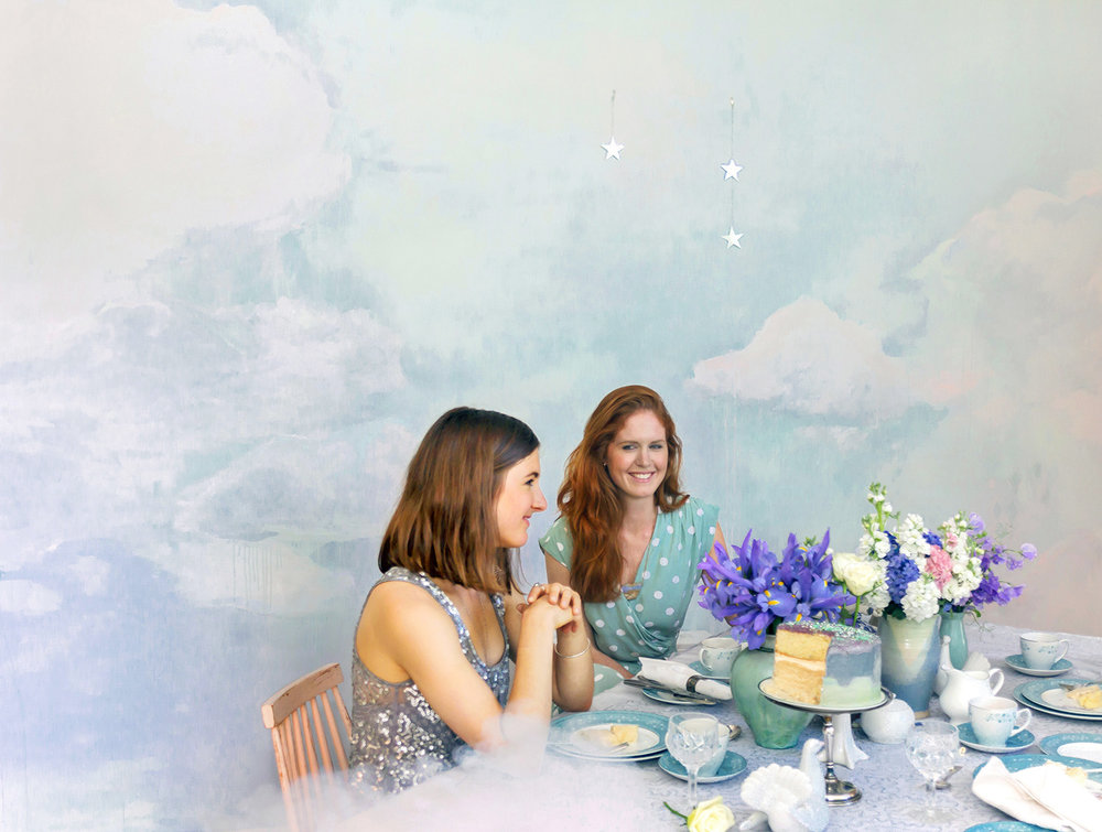Dreamily styled dinner party in the clouds, with painted cloud mural in pastel tones, the table features flowers, porcelain doves and an iced vanilla layer cake, models seated at table wear sparkly silver top and polka dot vintage wrap dress.