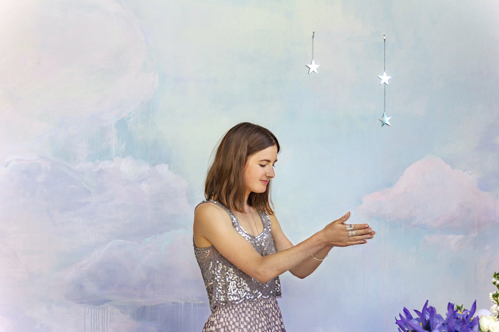 Dreamily styled dinner party in the clouds, with painted cloud mural in pastel tones, model wears sparkly silver top and silver jewellery and she rubs her hands together.