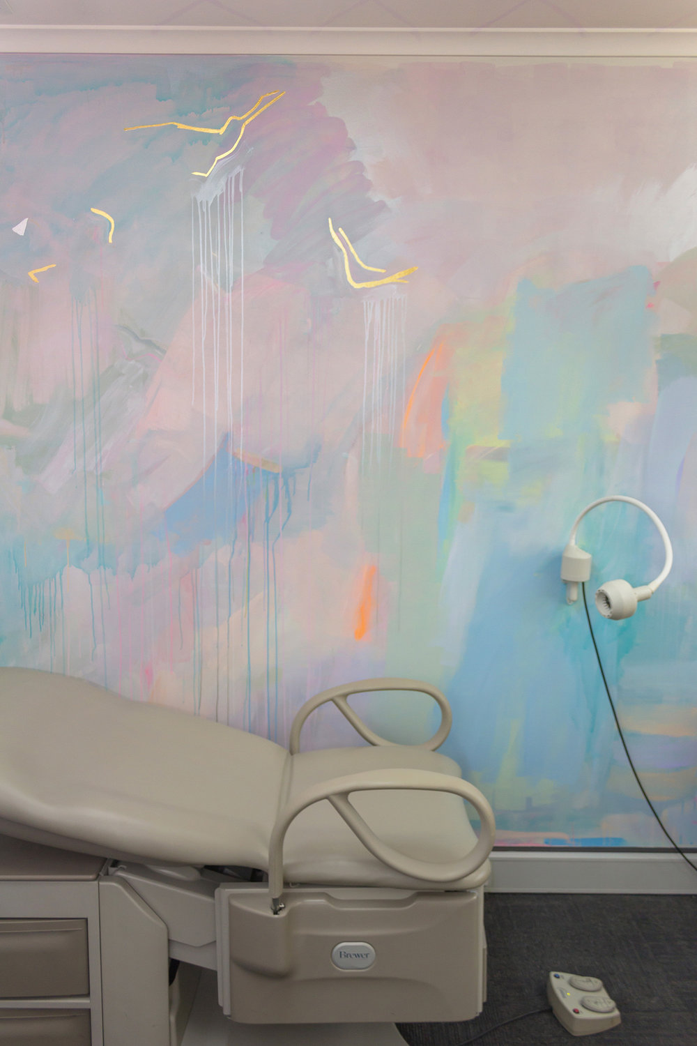 Pastel abstract mural painted in an OB/GYN office, featuring gold gilded birds flying across the wall and glowing metallic pink paint.