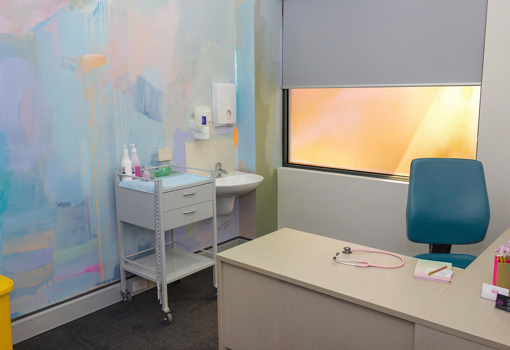 Abstract pastel mural painted in an OB/GYN office, featuring pink stethoscope and desk.