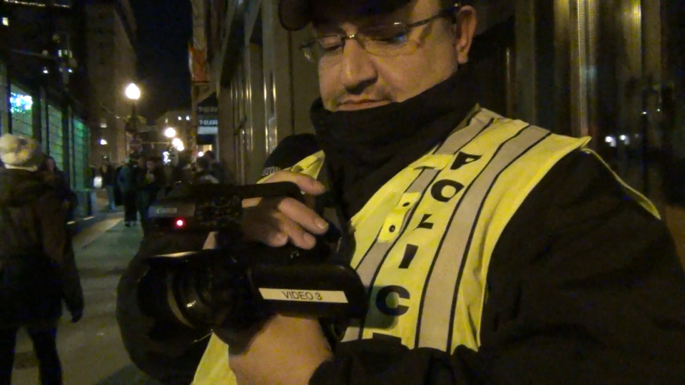 A Boston police videographer records demonstrators at a December 4 protest for Eric Garner.
