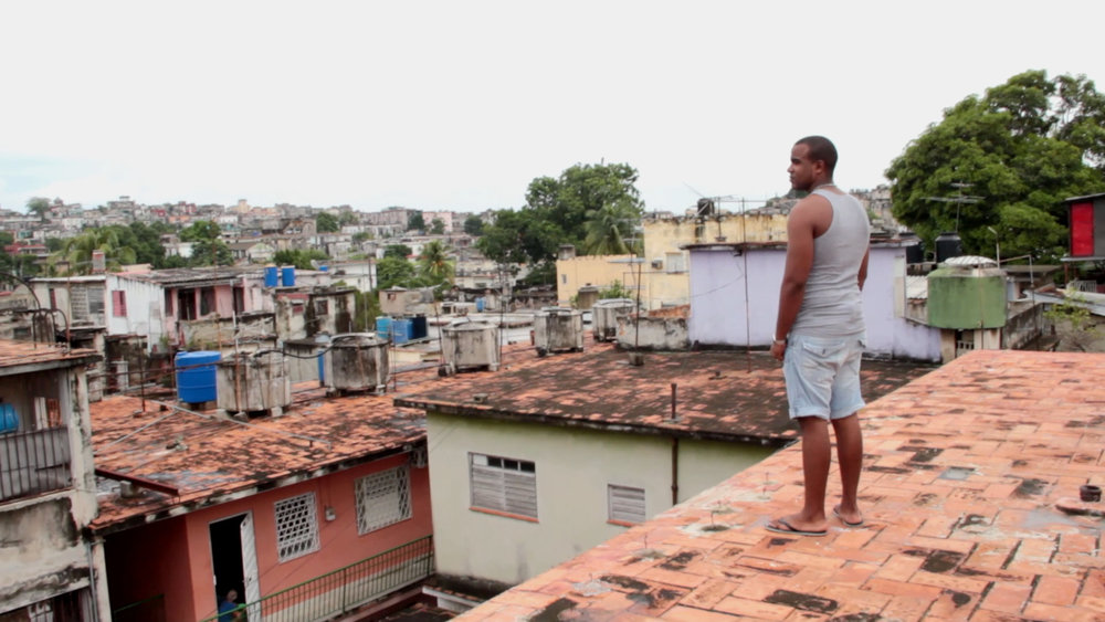 Yusniel looks over his neighborhood, so distant from the operatic fantasies he's passionate about.