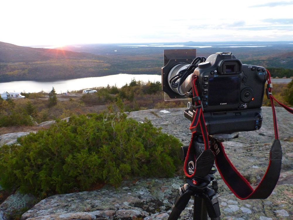 Using a graduated neutral density filter while shooting a sunset from Cadillac Mountain. The top half is darker than the bottom, to bring down the brightness of the sky closer to the brightness of the ground. The cord resting on top of the lens is an intervalometer to shoot time lapses.