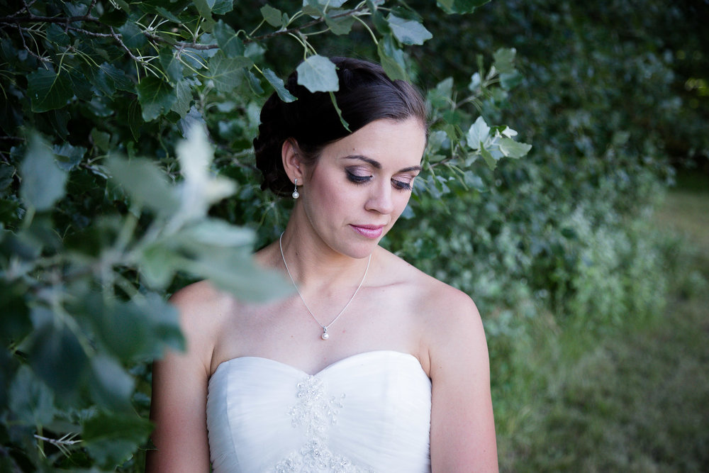 You can see here that the bride is in focus, but the leaves in the foreground, as well as the greenery behind her are not.