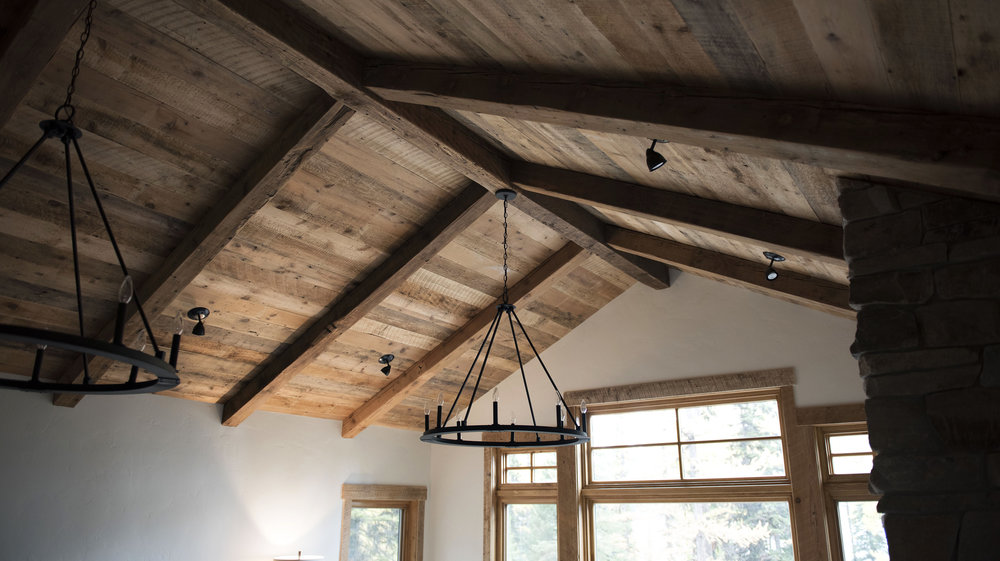 Exposed beams and reclaimed paneling make this ceiling the focus of the room. The black light fixtures give the whole room the true feeling of a mountain cabin.