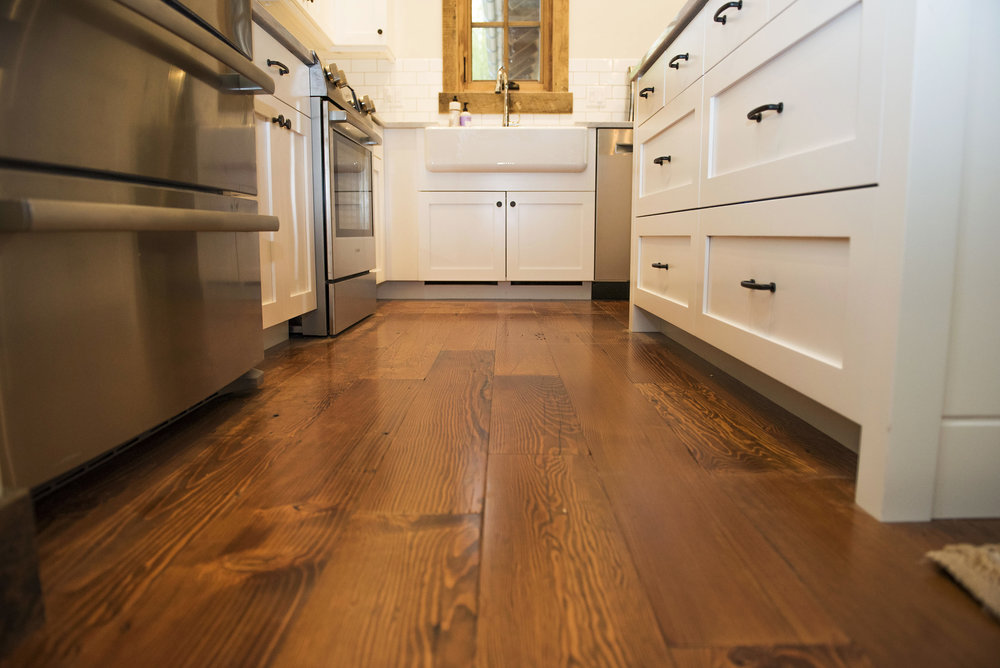 White cabinets and subway tile compliment the reclaimed wood floor that runs through the house. Black hardware also runs throughout the entire space keeping a clean and consistent look to the small space.