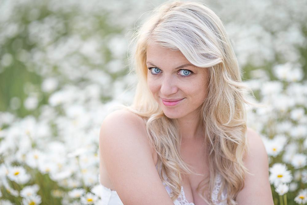 Portrait einer schönen blonden Frau im Magaritenfeld in Köln