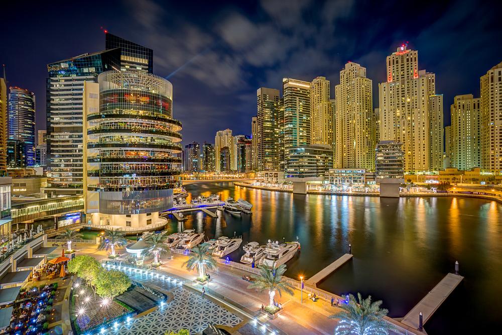 Dubai Marina bei Nacht mit vielen Hochhäusern im Hintergrund
