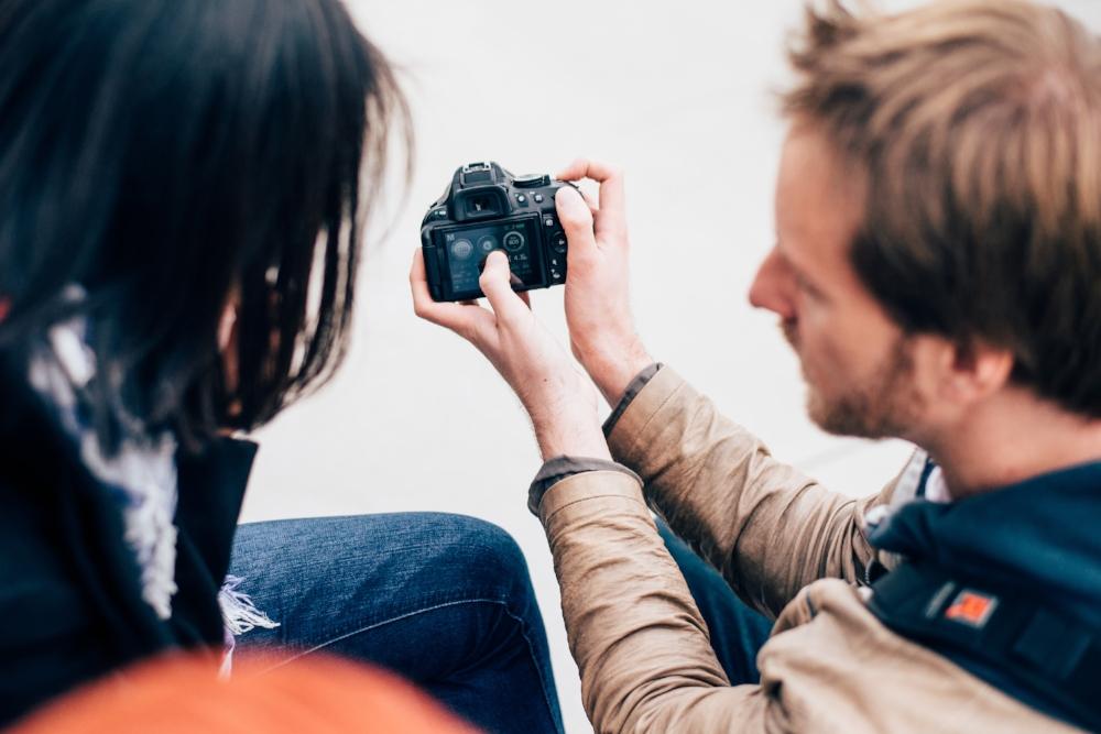 David erklärt einer Fotokursteilnehmerin Kameraeinstellungen