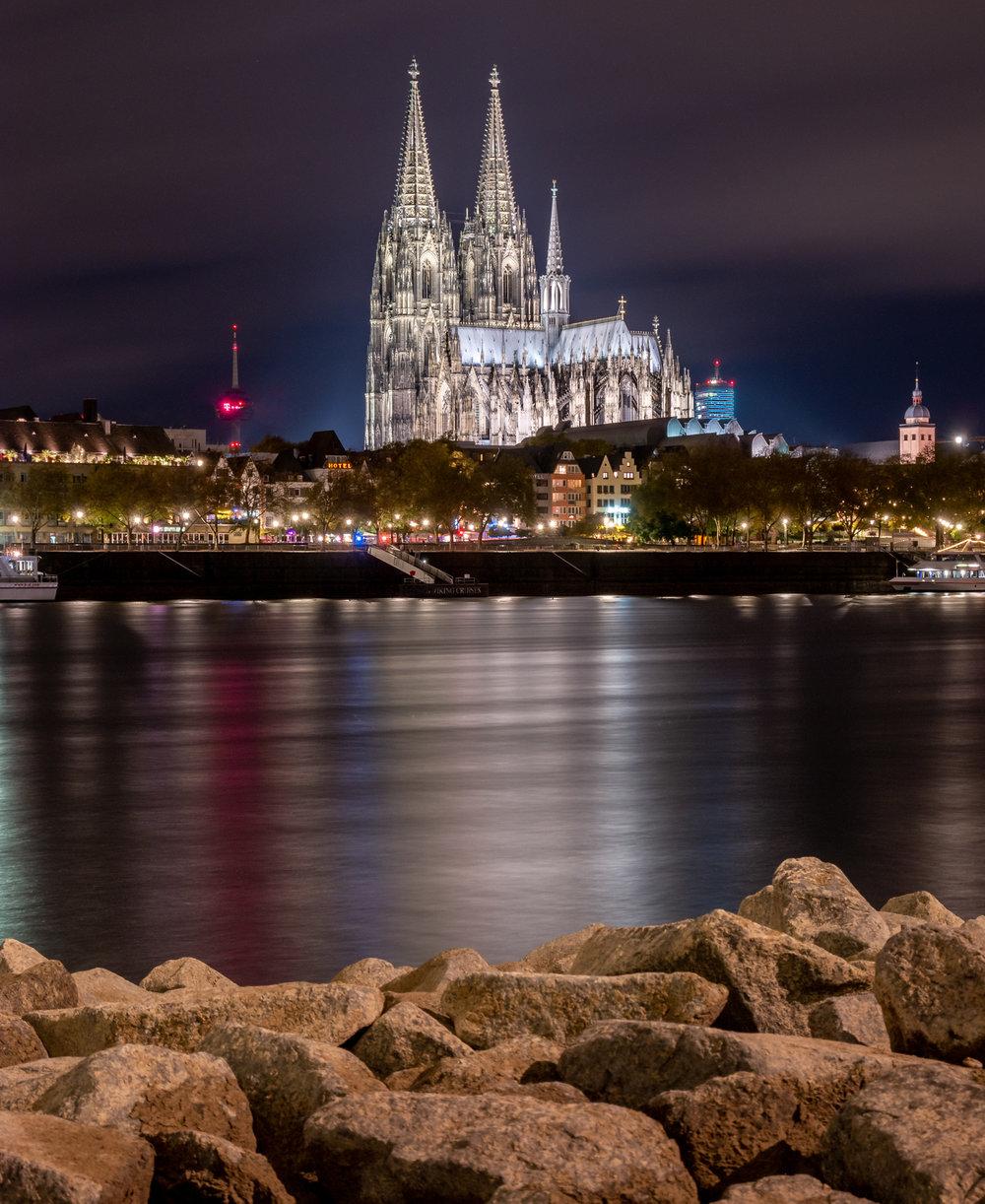 Dom mit Spiegelungen im Rhein mit Steinen im Vordergrund in der